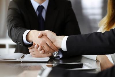 Business Handshake Across Desk