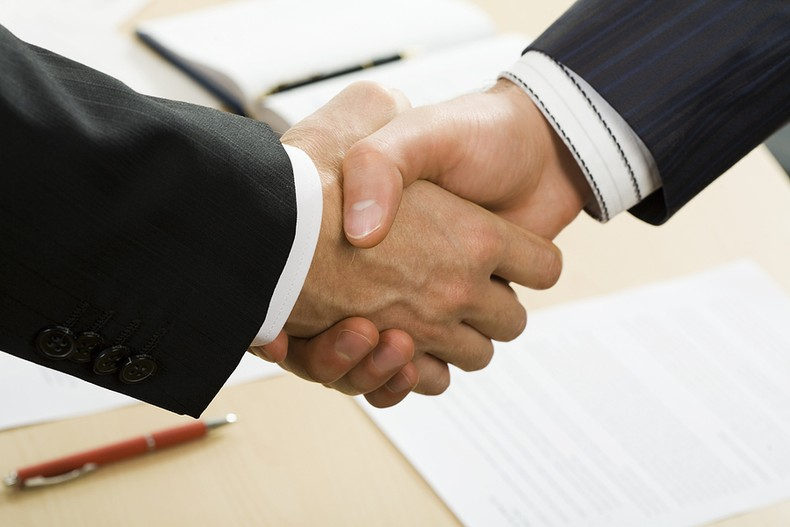 Business Handshake Over Desk