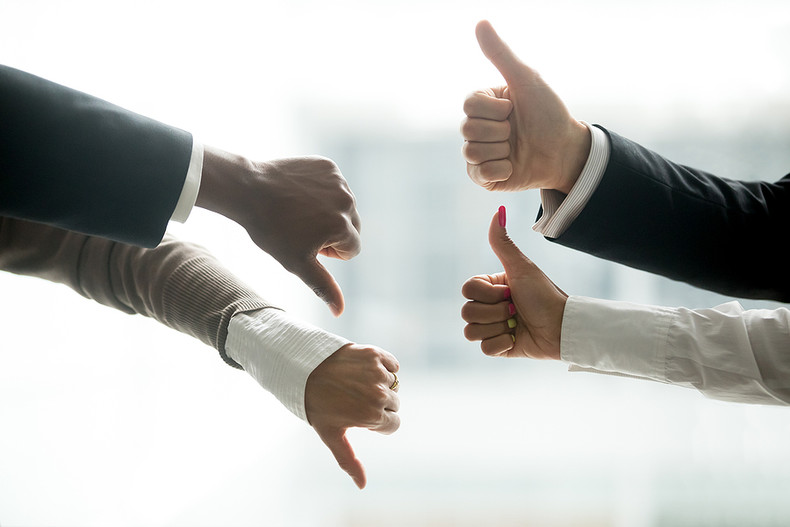 Business People Two Thumbs Up Two Thumbs Down Indicating a Difference of Opinion