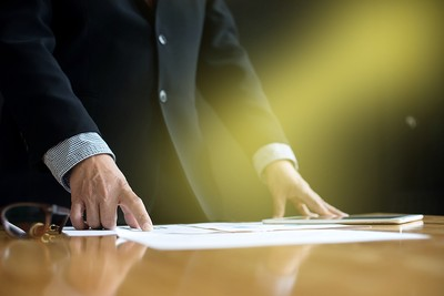 Businessman Standing at Boardroom Table