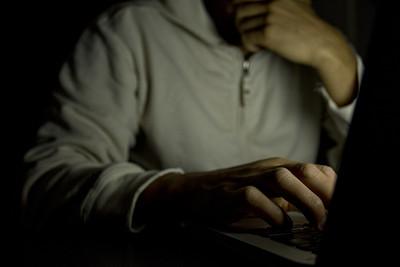 Man Typing on Laptop in Dark Room