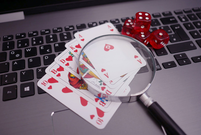 Poker Hand and Magnifying Glass on Keyboard
